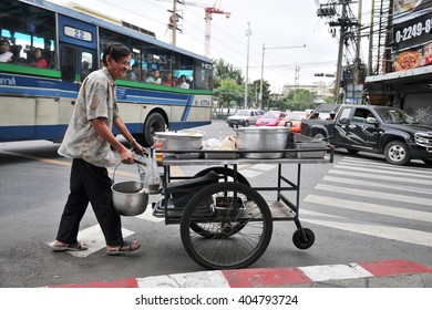 Bangkok, Thailand - December 17, 2010: A hawker pushes a mobile kitchen along a city centre street.