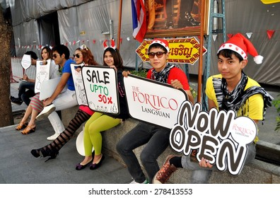 Bangkok, Thailand - December 18, 2011:  A group of young Thais holding advertising signs promoting the Portico restaurant and shopping center on Lang Suan Road