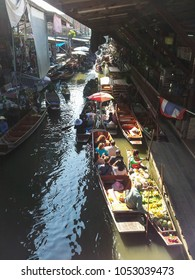 Bangkok, Thailand - December 18, 2013: tourists wondering and shopping around in in wooden boats at floating market near Bangkok