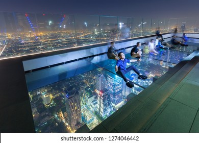 Bangkok / Thailand - December 19 2018: Man and Woman testing glass tray for safety excited highest outdoor observation area at King power mahanakhon landmark high rise building sunset and night view