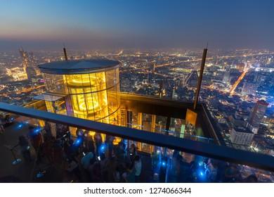 Bangkok / Thailand - December 19 2018: Outdoor observation at 314 meters with hydraulic glass lift panorama view looking bangkok city at sunset and night light view rooftop bar king power mahanakhon