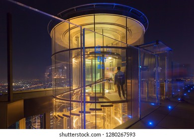 Bangkok / Thailand - December 19 2018: Outdoor observation deck at 78th floor with golden light hydraulic glass lift and stairway bangkok city panorama view at night rooftop bar king power mahanakhon