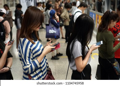 Bangkok Thailand - December 20, 2017: The passengers line up to waiting for MRT subway train and using smartphones to kill time in rush hour, Mobile phone addiction lifestyle daily, Social technology