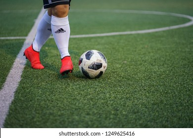 Bangkok / Thailand - December 2018 : Football player is training football on artificial grass pitch with Adidas Predator 19.3 Laceless shoe. This football boots series is presented by Pogba and Ozil.