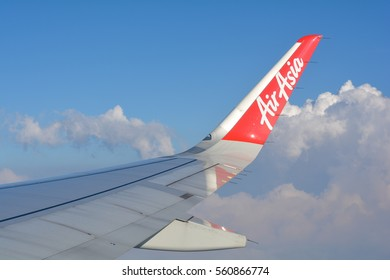 Bangkok, THAILAND - December 21, 2016: Image form window airplane, view of Wing of Thai AirAsia HS-BBY Airbus A320-200 Take off from Bangkok Don Muang airport to Chiang Mai flying on sky cloudy day