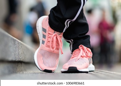 BANGKOK, THAILAND - DECEMBER 21, 2018 : Women wearing adidas swift run w 2017 sports shoes for running for woman on street outdoor - illustration editorial