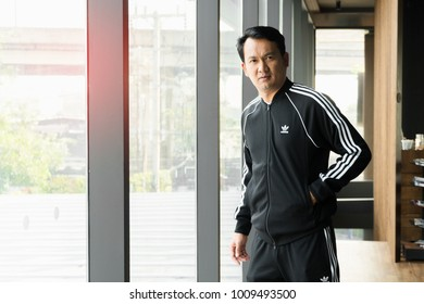 BANGKOK, THAILAND - DECEMBER 21, 2018 :A man wearing new collction adidas original jacket and sweatpants,  A German multinational corporation that designs and manufactures sports shoes, clothing