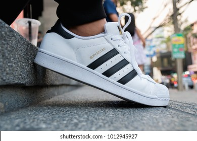 BANGKOK, THAILAND - DECEMBER 21, 2018 : Man wearing adidas Superstar shoe white color stripes black with popular fashion Thailand on urban background