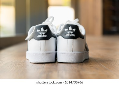 BANGKOK, THAILAND - DECEMBER 21, 2018 : The adidas Superstar shoe white color stripes black on wooden floor  in cafe with popular fashion Thailand.