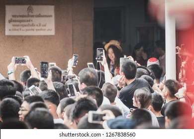 Bangkok, Thailand - December 21, 2018: Crowd at Assumption College Christmas Fair taking photo of members of BNK48, a popular idol group, before their performance. Focus on the crowd at the front.