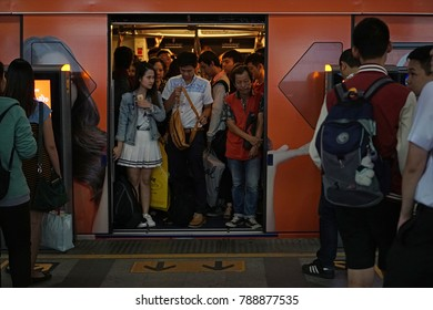 Bangkok Thailand - December 22, 2017: Full passengers packed inside BTS skytrain arrived and people lined up  waiting on platform in rush hour, The Bangkok Mass Transit System