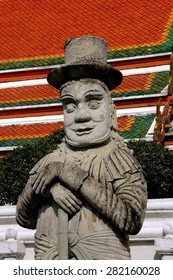 Bangkok, Thailand - December 23, 2005:  Giant stone Marco Polo statue wearing a top hat in a courtyard at 16th century Wat Pho