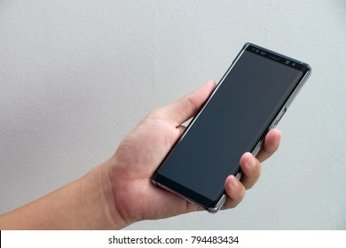 BANGKOK, THAILAND - December 23, 2017 : Business man hold Samsung Galaxy Note 8 with hand on light blue concrete background. It is the flagship smartphone with android os.