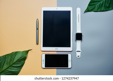 BANGKOK, THAILAND - December 23, 2018: Flate lay of Apple device products iPhone, iPad and Apple Watch on yellow and gray background