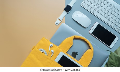 BANGKOK, THAILAND - December 23, 2018: Flate lay of Apple device products Macbook Pro, iPhone, iPad on yellow and gray background