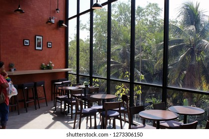 Bangkok, Thailand - December 24th, 2018: A customer looks at the view of tropical trees through a large window inside a Café Amazon, a chain of Thai cafés founded by PTT Public Company Limited.