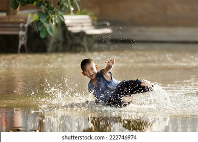 BANGKOK, THAILAND, DECEMBER 25, 2011: Dressed little boy having fun slipping in a flooded square near the river in Bangkok, Thailand