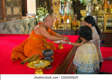 BANGKOK, THAILAND - DECEMBER 27, 2018: The Buddhist monk ties a string amulet on a hand to the woman in the Buddhist temple