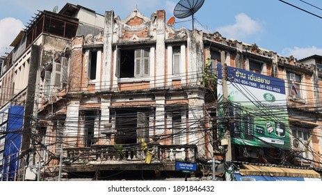 BANGKOK, THAILAND - DECEMBER 27, 2020: View of electric cables in front of a decrepit building on December 27, 2020 in Thai capital Bangkok