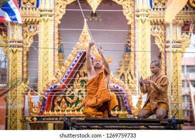 BANGKOK, THAILAND – DECEMBER 27: Two monks sit on the scaffolding to prepare the venue for the New Year's Eve to welcome the New Year on December 27, 2018 in Bangkok, Thailand.
