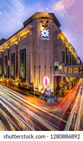 BANGKOK, THAILAND - DECEMBER 28, 2018: Central Chidlom Department Store on greetings season with Christmas street light decorations in twilight with traffic light trail.