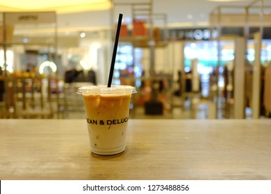 BANGKOK, THAILAND - DECEMBER 28,2018 : A glass of iced latte coffee on a wooden dinning table in Dean & Deluca shop with blurred a department store area in Bangkok, Thailand