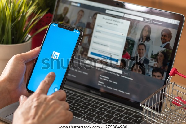 BANGKOK, THAILAND - December 29, 2018: LinkedIn app, business and employment-oriented service for job, career search application logo on mobile smart phone iPhone devices in businessman's hand at work
