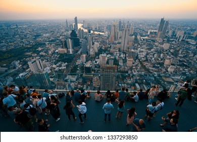 Bangkok, Thailand - December 3 ,2018: Many tourists enjoy sunset on rooftop of the King Power Mahanakhon building high above Bangkok, Famous and tallest building of Bangkok.