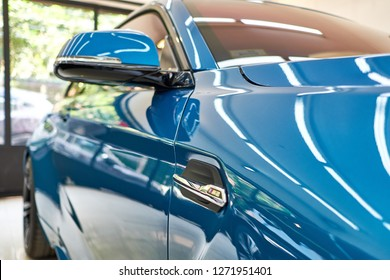 BANGKOK, THAILAND - DECEMBER 30, 2018: The side view of BMW M2 coupe sports compact car. Selective focus. Body curve and side mirror with shiny blue paint & reflection on bonnet after polishing