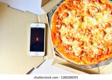 Bangkok, Thailand - December 30, 2018: Top View of Smartphone with Netflix Application on the Screen and Pizza on the Side