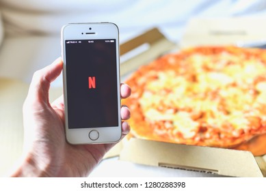 Bangkok, Thailand - December 30, 2018: Hand Holding a Smartphone with Netflix Application on the Screen and Pizza in the Background