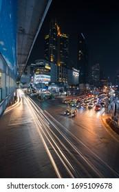 Bangkok, Thailand - December 30, 2019: Night traffic light trails on the road at Asoke, Bangkok, Thailand.