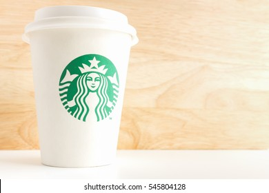 BANGKOK ,THAILAND - December 31, 2016 : Cup of Starbucks coffee with new logo on wood background