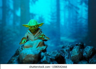 Bangkok, Thailand - December 5,2019: A setting display of Master Yoda, an action figures, sitting on the rock with forest background.