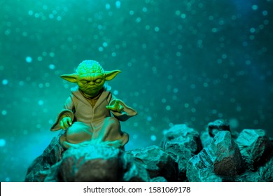 Bangkok, Thailand - December 5,2019: A setting display of Master Yoda, an action figures, sitting on the rock with snowing background.