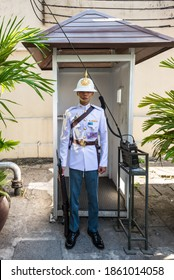Bangkok, Thailand - December 7, 2019: Soldier of the royal guard in patent leather with a radio station nearby at the Royal Grand Palace in Bangkok, Thailand.