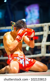 Bangkok, Thailand - December 8, 2010: Male muay thai kickboxer kneeling and covering his face with gloves during traditional pre-fight ritual called the wai khru