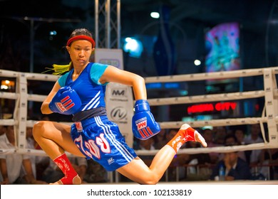 Bangkok, Thailand - December 8, 2010: Female muay thai kickboxer performing a knee down kicking routine during a pre- kickboxing dance called the wai khru at amateur women's match