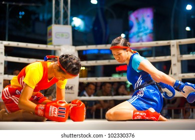 Bangkok, Thailand - December 8, 2010: Two female muay thai fighters side by side kneeling, bowing, performing kickboxing ritual dance called the wai khru before the amateur match