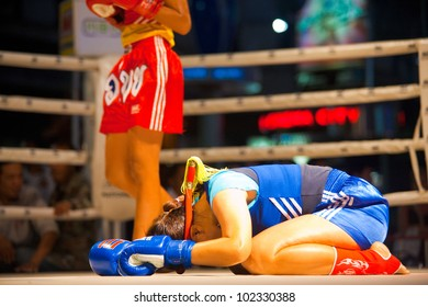 Bangkok, Thailand - December 8, 2010: Female muay thai fighter in blue bowing her head on the ring canvas performing a kickboxing ritual called the wai khru before amateur outdoor match