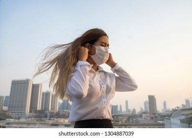 Bangkok Thailand encountered heavy dust pollution problems.Asian women wearing air-protective masks with dust in the air are polluting the capital of Bangkok.