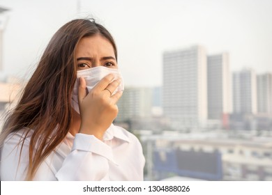 Bangkok Thailand encountered heavy dust pollution problems.Asian women wearing air-protective masks with dust 2.5 Particulate Matte in the air are polluting the capital of Bangkok.