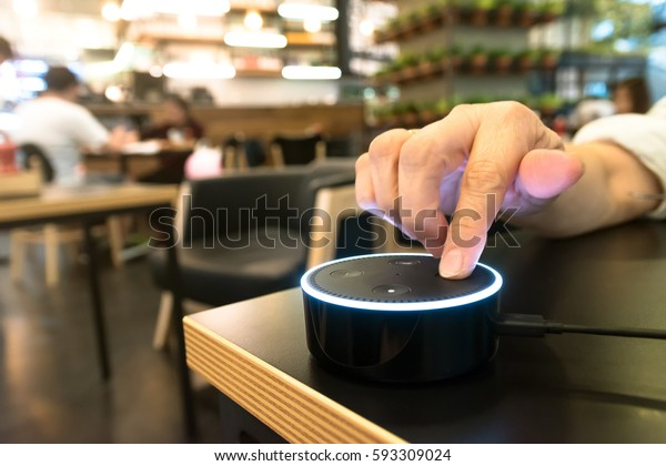 BANGKOK, THAILAND - Fabruary 2 : Finger point to Amazon Echo dot version 2, the voice recognition streaming device from Amazon in coffee shop on Fabruary 2 2017 in BANGKOK, THAILAND