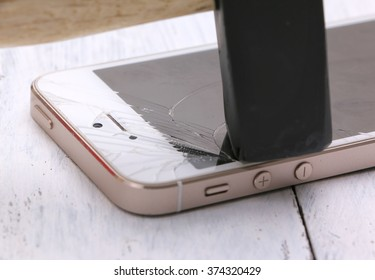 Bangkok, Thailand - Feb 01: Studio shot of an iPhone 5 with seriously broken retina display screen with hammer on wooden  on Feb 01, 2015. iPhone 5 is a smartphone developed by Apple Inc.