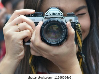 BANGKOK, THAILAND - FEB 16, 2018: Beautiful female Thai photographer holds her Nikon FM2 SLR camera with both hands and takes a photo, on Feb 16, 2018.