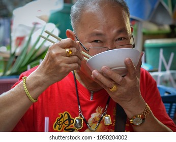 BANGKOK, THAILAND - FEB 17, 2018: Elderly Thai Chinese man lifts a white plastic bowl with noodle soup to his mouth and eats his noodles with chop sticks in Bangkok's Chinatown, on Feb 17, 2018.
