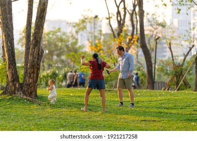 Bangkok, Thailand - FEB 19, 2021: The family took their child for a walk in the park. Father holding a cellphone preparing to take a picture of his child.