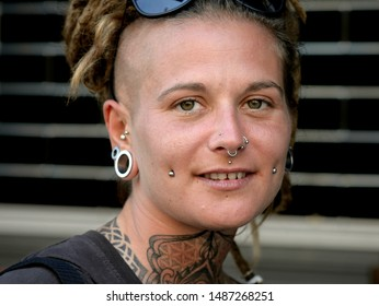 BANGKOK, THAILAND - FEB 23, 2019: Young French traveller with facial piercings, tattoos and dreadlocks smiles for the camera, on Feb 23, 2019.