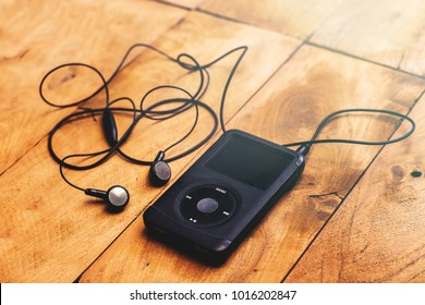 BANGKOK, THAILAND - FEB 3: Close up on iPod classic 120 GB in black case with headphone on a wooden table background on February 3, 2017 in Bangkok, Thailand.