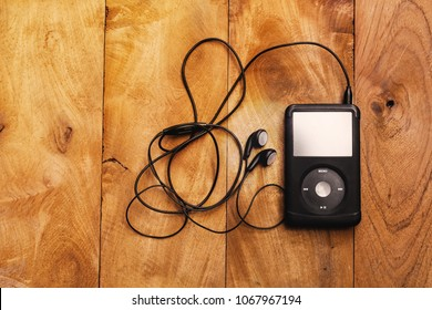 BANGKOK, THAILAND - FEB 3: Top view of iPod classic 120 GB in black case with headphone on a wooden table background on February 3, 2017 in Bangkok, Thailand.